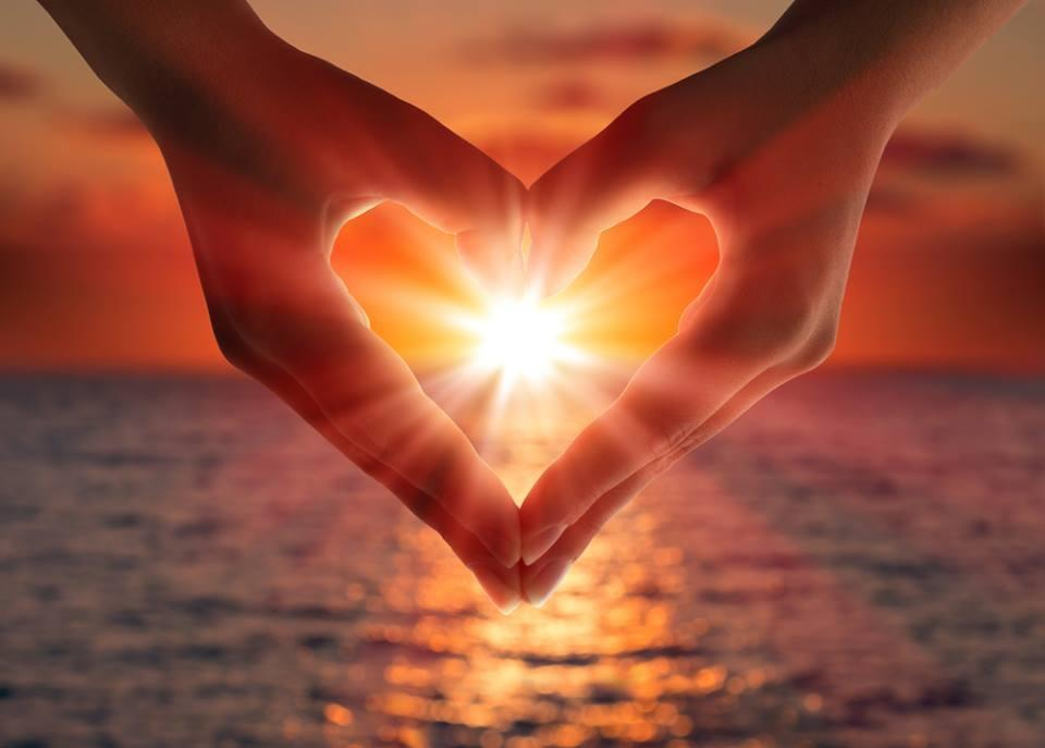 Heart shape made with two hands and sunset peaking through