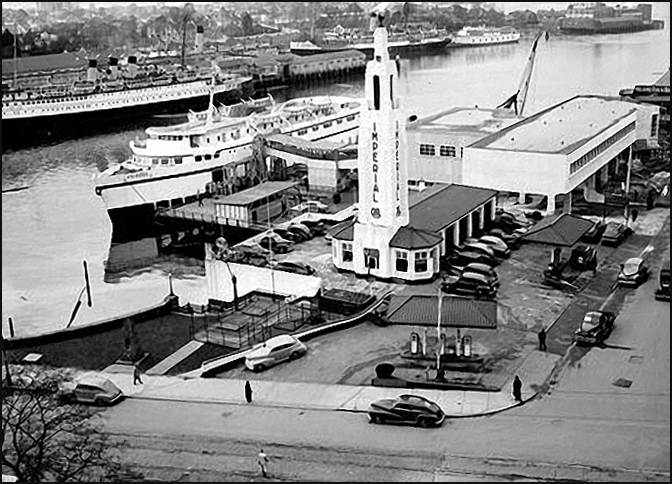 Imperial Garage with a float plane navigation light atop its tower. Black Ball's MV Chinook in the foreground as a BC Coast Steamship lies at her moorings across the harbour by the CP Steamship Termin