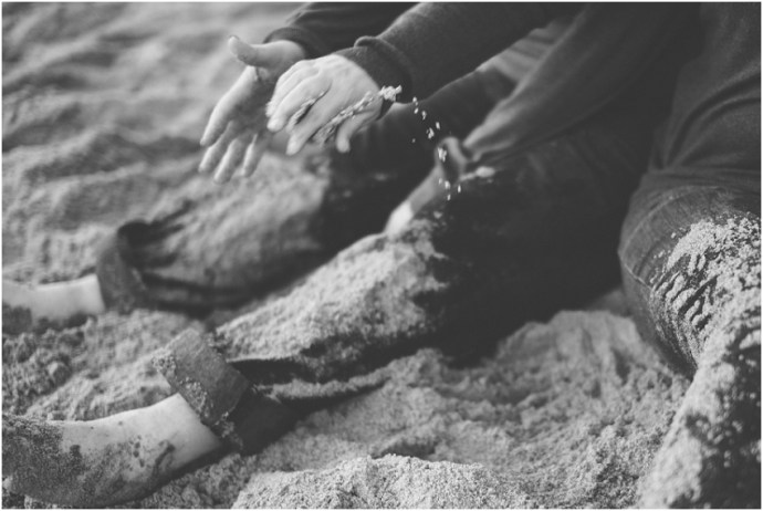Two brides playing with sand during an engagement session at venice beach