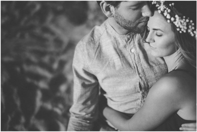 Black and white image of a girl wearing flower crown hugging her fiance