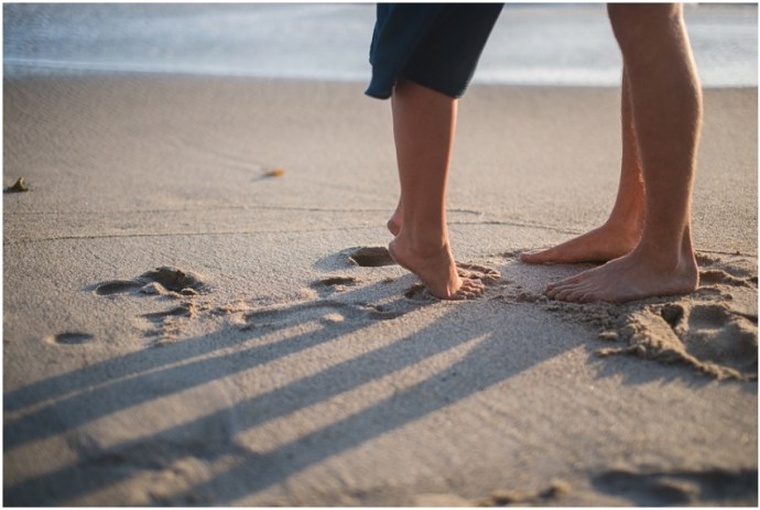 Girl tiptoeing on a beach to kiss her fiance