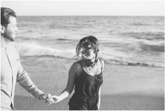 Black and white portrait of a couple running along the beach holding hands