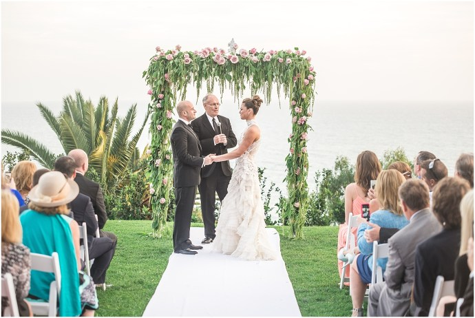Wedding Ceremony at the Bel Air Bay Club lawn, under a green arch with beautiful pink flowers