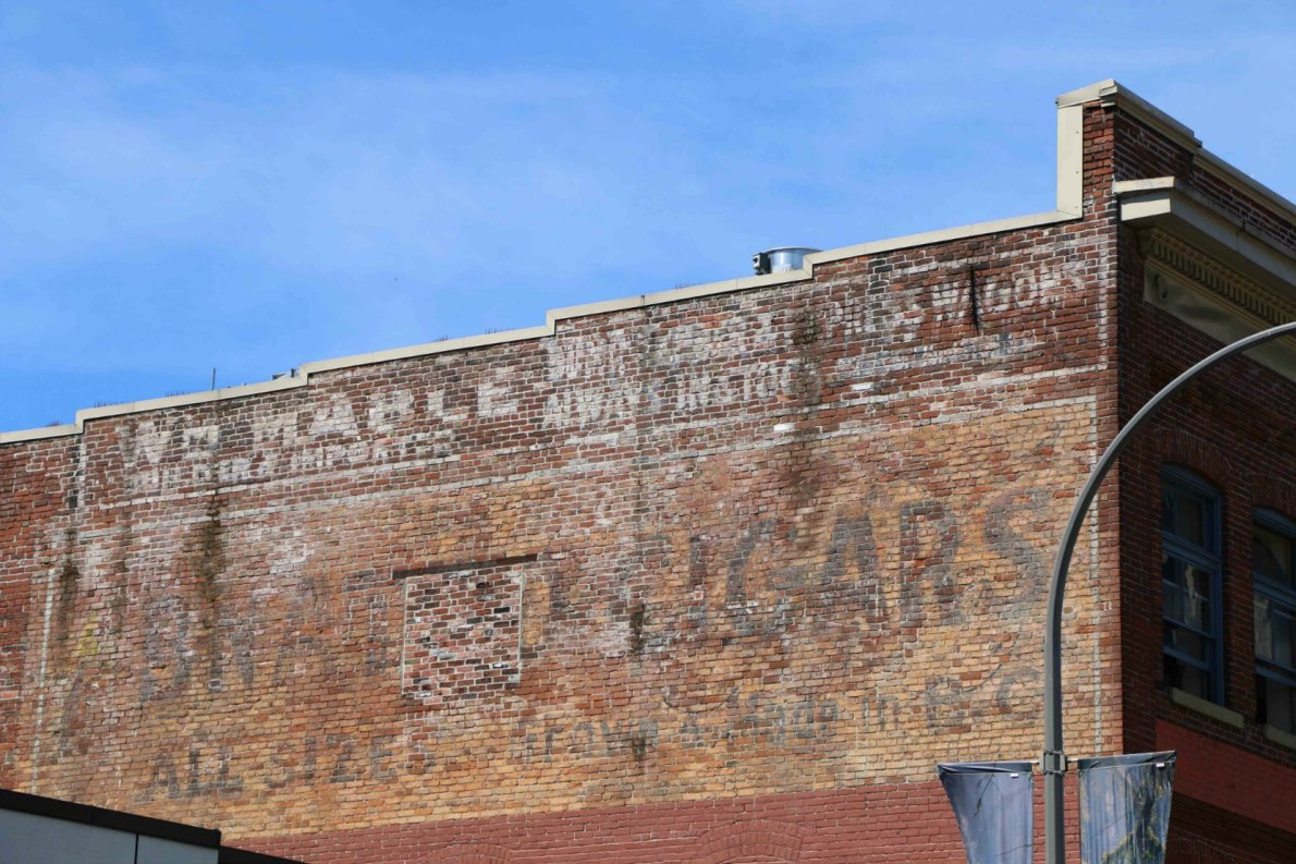 The east wall of 713-715 Johnson Street still shows the early 20th century painted signs for Mable Carriage Works and other businesses which operated in this building.