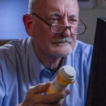 A concerned man, with eyeglasses down on his nose, sits behind a computer and reads up on his pills