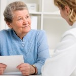 Patient holds list of questions while looking at doctor