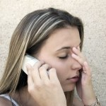 A young woman buries her head in her face during a phone call.