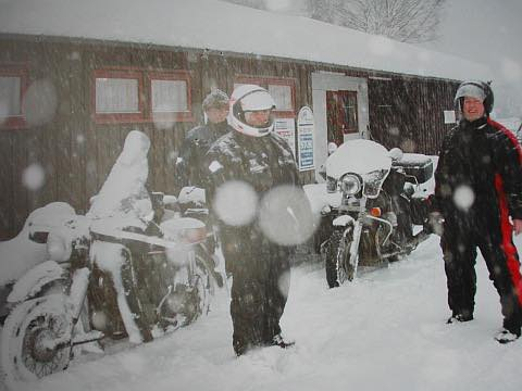 Dos hombres de pie sobre sus motos entre una gran nevada