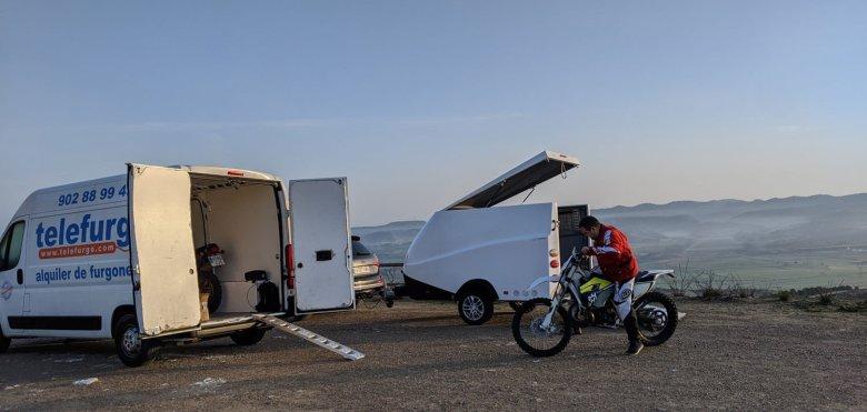 Maniobra en moto frente a furgoneta y remolque abiertos