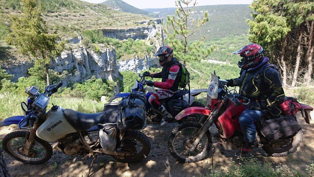 Tres motos paradas en un camino con vistas panorámicas