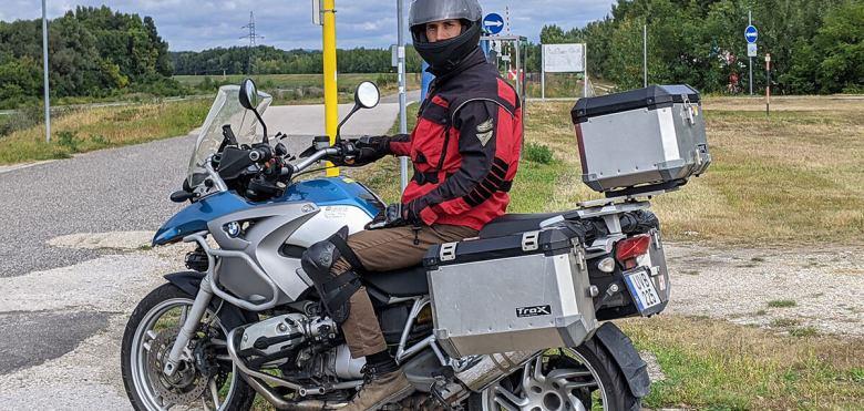 Moto y piloto parados ante una señal de tráfico que muestra a Bratislava a 14,5km.
