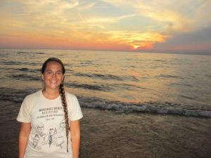 Photo of the author, Cecelia Rose LaPointe, wearing a white T-shirt and one long braid down their shoulder, standing in front of a beach at sunset, smiling.