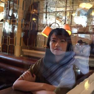 Author photo of Chia-Lun Chang, sitting at a restaurant with her arms crossed, with a thoughtful look. Lights reflect against the image, as if it's taken through glass.