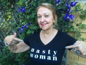 """Grace Bauer wearing a short sleeve blue """"nasty woman""""t-shirt"""