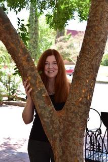 Julie Kane looking through a v-shaped tree.