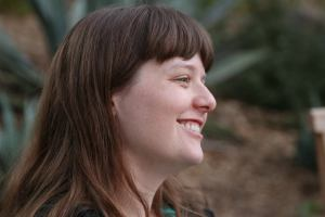 Katharine Coldiron smiles in profile, looking away from the camera. She has dark hair and there are trees behind her.