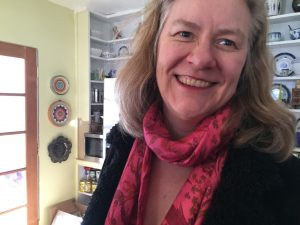 Photo of the author, Sarah Browning, smiling, wearing a red scarf and black shirt, and loose shoulder-length hair.