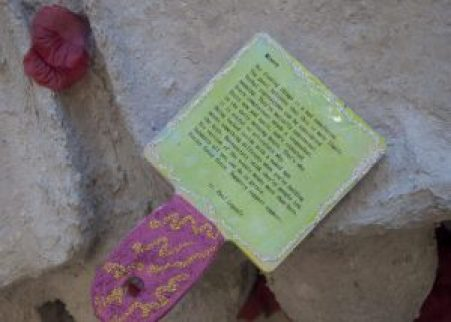 Close up photograph of a pink decorated paddle with gold squiggle designs, lying poem-side up on a plaster platform. The poem is titled Misery. A lone cluster of flower petals lies off to the side of it.