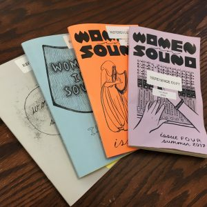 Photograph of four issues of the Women in Sound Zine, one white, one light blue, one orange, and one lavender, all with black type, on a wood-grained table.