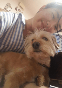 A selfie of the author, a Korean person with short hair and a striped shirt, with their dog, who is tan with curly fur.