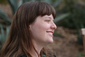 Profile shot of smiling white woman with brown hair and bangs against an indeterminate natural background.