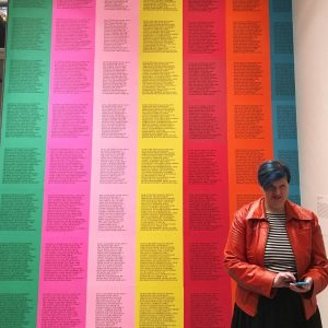 """Sarah Nichols, a white woman with blue hair wears a red faux leather jacket over a black and white horizontal striped shirt. She is standing in front of artist Jenny Holzer's """"Inflammatory Essays,"""" text printed on 7 colors of paper arranged in columns, creating a rainbow. The text cannot be read clearly."""
