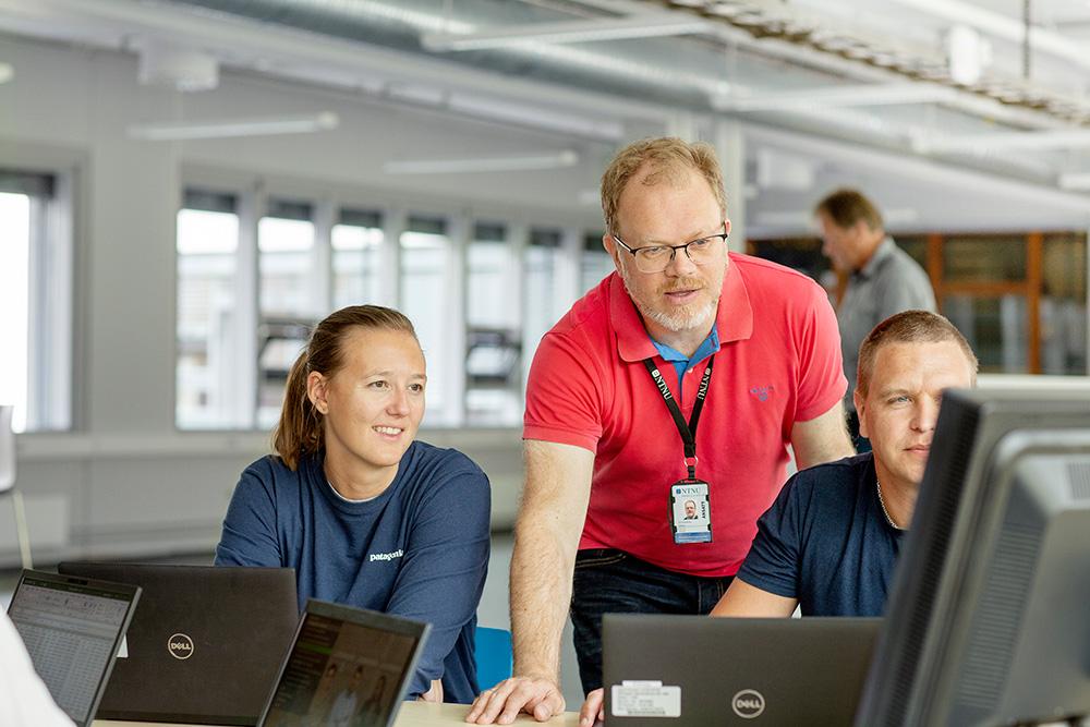 Førsteamanuensis Jan Alexander Langlo står bak studentene som jobber på datamaskin
