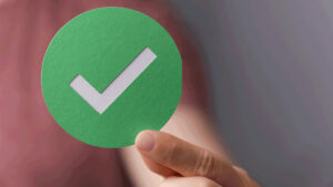 A hand holing up a check mark to signify an online video platform that passes evaluation.