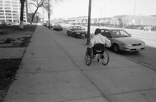 Mario Bailey travelling on the sidewalk in his wheelchair along State Street