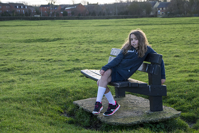relaxing on a bench, you can see why she was cold. - Girl on a bench in skirt and jumper