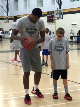 Paul George works with a camper at his camp at Avon High School.