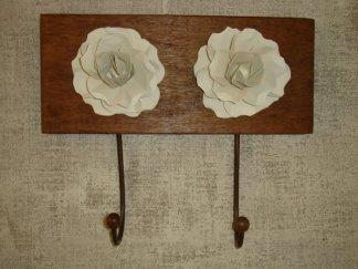 Cabideiros com rosas de metal sobre um suporte de madeira