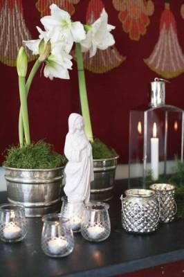 Arranjo com velas, flores e sua santa protetora