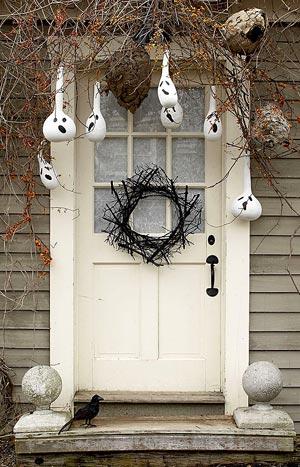 Cabaças com caras de fantasmas na entrada da casa