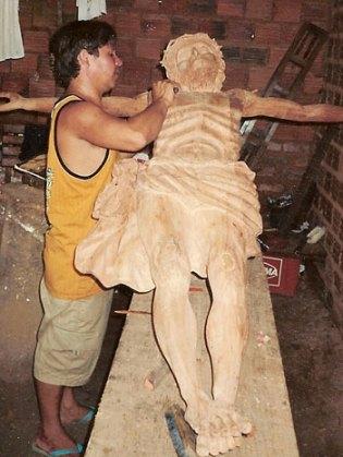 Amaral trabalhando na escultura em madeira de um Jesus Cristo crucificado