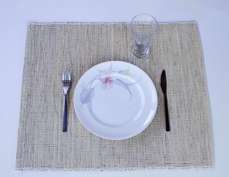 Um jogo americano com duas peças feito com palha de carnaúba e algodão