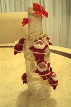 Mini papais Noel enfeitam a garrafa na reciclagem para o natal