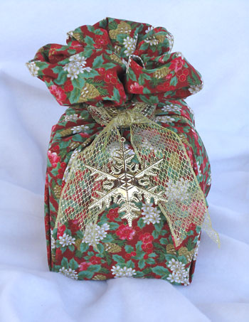 Envolvi o nó do furoshiki com um laço de fita e um pingente de natal