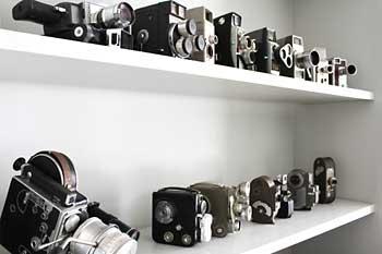 Máquinas fotográficas e filmadoras expostas em prateleira