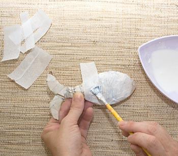 Cole tiras de papel de seda sobre a figura
