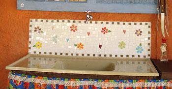 Sobre a pia um barrado em mosaico de azulejos