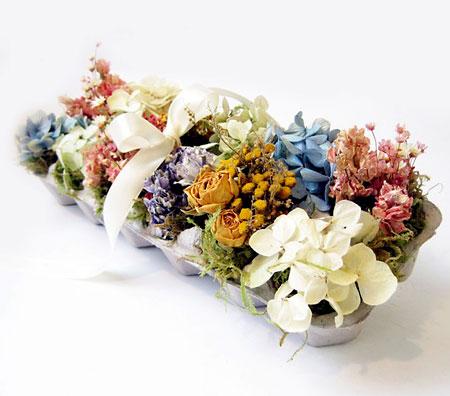 Arranjo de flores desidratadas em caixa de ovos
