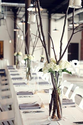 Enfeites de mesa de festa com grandes vasos e galhos