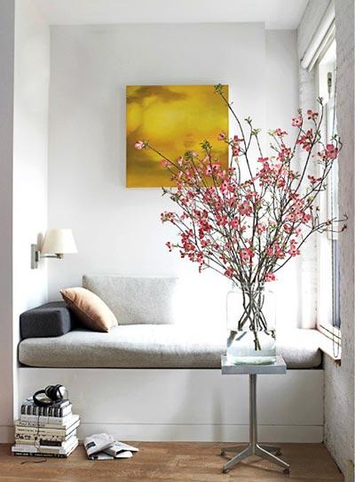 Galão de vidro com galhos de floradas da época