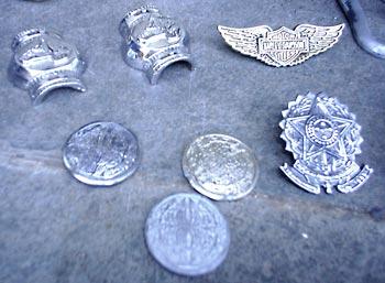 Peças em fundição de metal como brasões, botons e fivelas