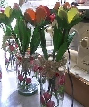 Potes de vidro com flores de caixa de ovos