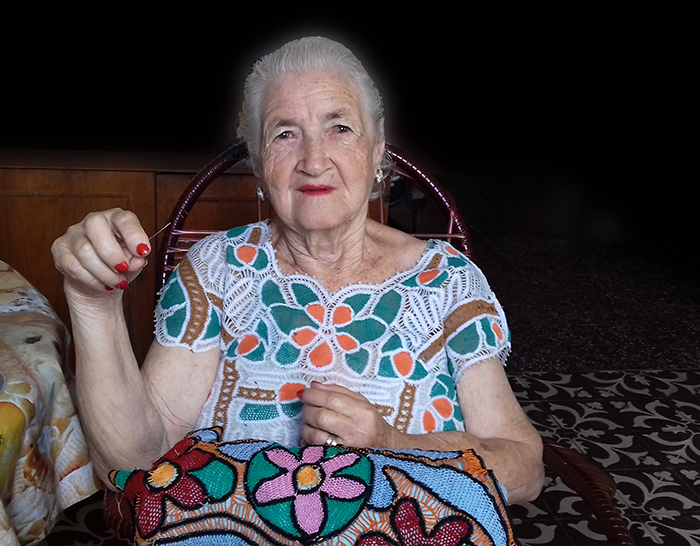 Dona Odete tecendo suas rendas coloridas