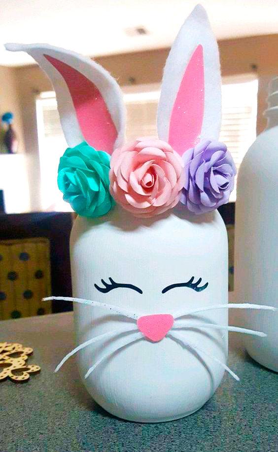 Orelhas de feltro e flores de papel no pote de vidro que é um coelho