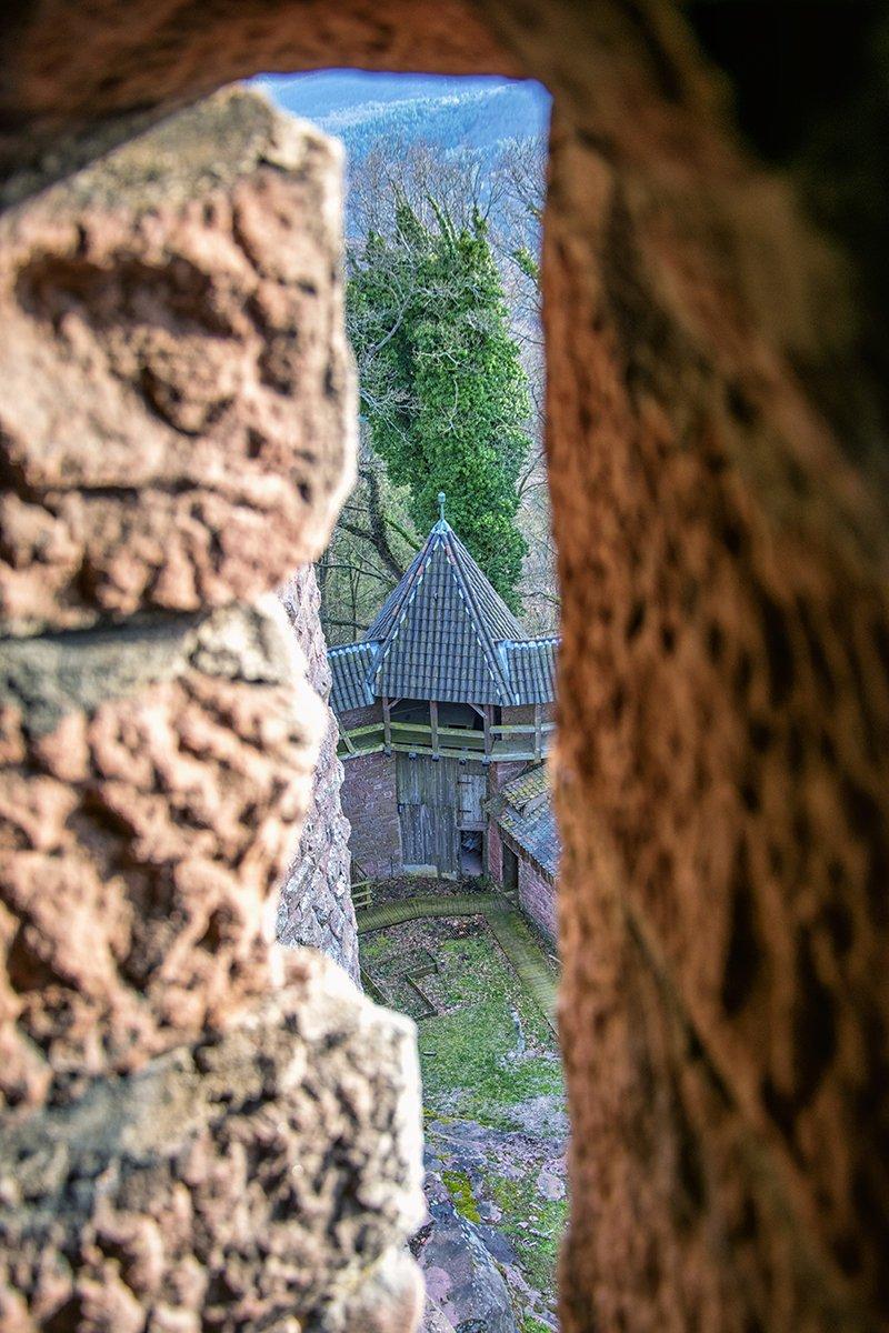 Entrevoir la cours intérieur depuis les petites fenêtres du Château
