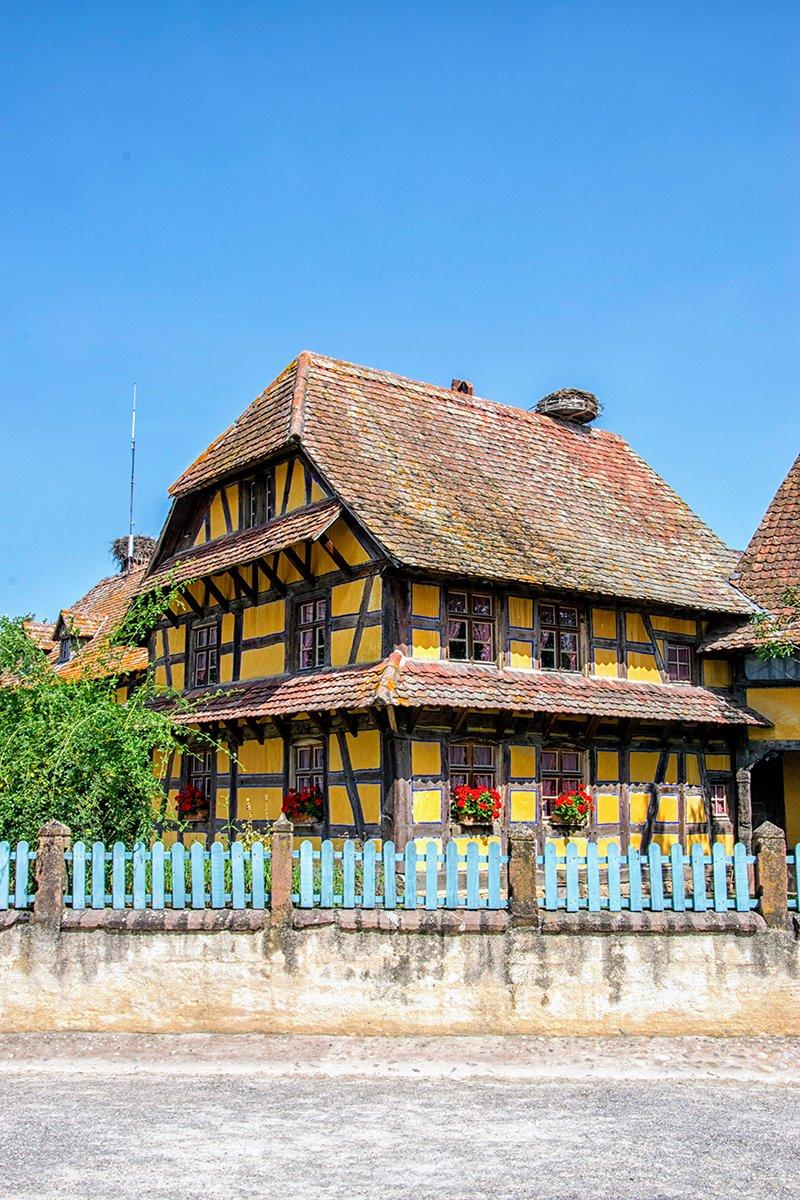 Maison jaune à colombages et barrière bleue